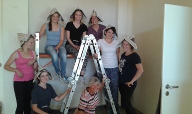 Sieben DHBW Studentinnen mit Mentorin auf und unter Arbeitsgerüst und Leiter